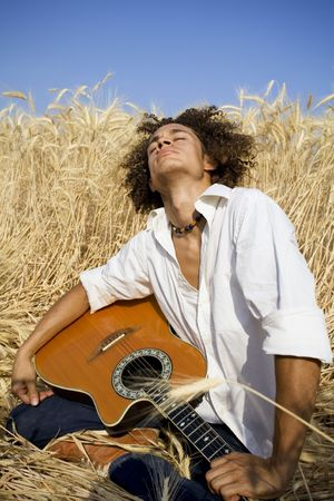 cool guy laying in a cornfield playing guitar Stock Photo - 501331