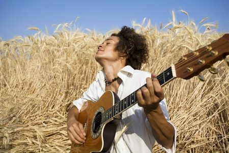cool guy laying in a cornfield playing guitar