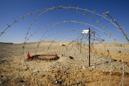 lethal: barbed wire at the border of a mine field Stock Photo