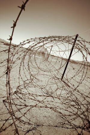barbed wire at the border of a mine field Stock Photo - 501322