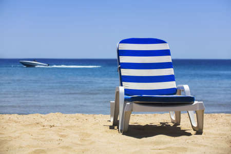 sun bed on a white beach and a yacht in the distance Stock Photo - 509969