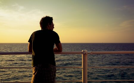 guy standing on a boat and looking at the sea photo