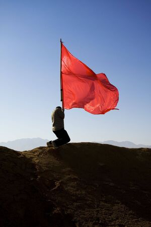 windy energy: man pushing a red flag into the ground