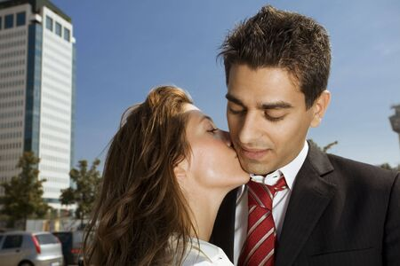 two colleagues kissing each other during a break from work photo