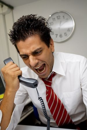 screaming head: angry businessman screaming on the phone