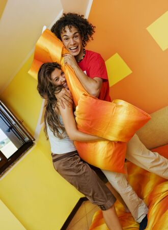 young couple playing with pillows