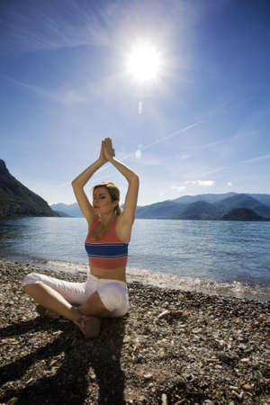 joga: blond girl doing yoga nearby the lake Stock Photo
