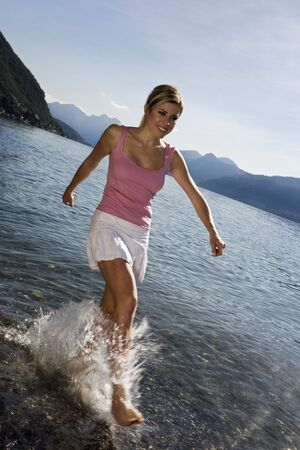 woman squirt: blond girl running on the shore and splashing water