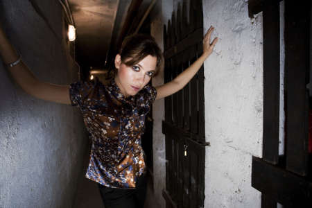 standing alone: girl standing alone against a wall in a basement