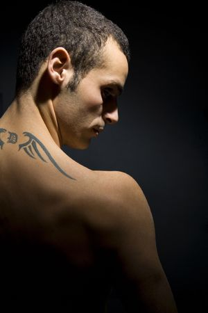 dark skin: man seen from behind showing his tattoo on his shoulders