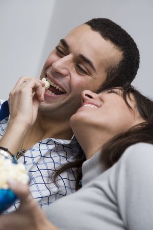 young couple watching tv at home and laughing