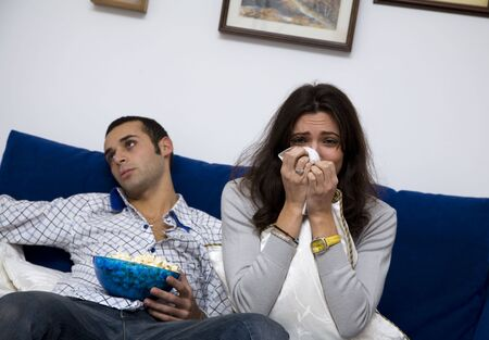 food fight: young couple watching a romantic movie on tv. The guy is quite bored.... Stock Photo