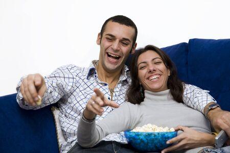 pareja viendo tv: pares j�venes que miran la TV en el pa�s y re�r Foto de archivo