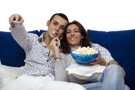 young couple watching tv at home and laughing photo