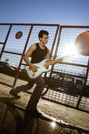 reverb: cool guy playing his guitar against sunlight