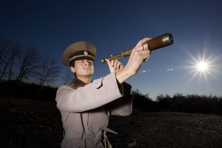 Word War II: suspicious russian soldier looking for enemies using a spyglass photo