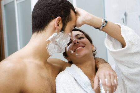 morning routine: the guy shaving and the girl (trying to) apply her make-up photo