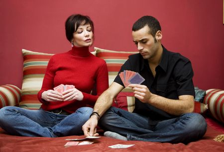 rummy: young couple having fun playing cards at home
