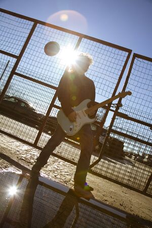 cool guy playing his guitar against sunlight photo