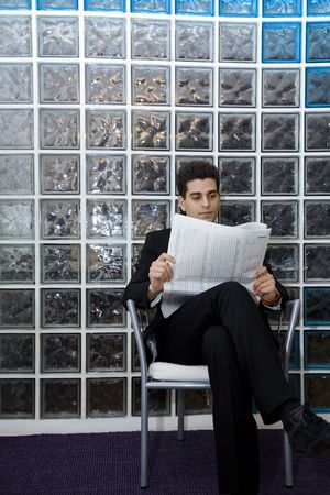 hard worker: business man sitting in a waiting room and checking stocks photo