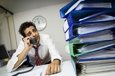 exhausted businessman in his office surrounded by files