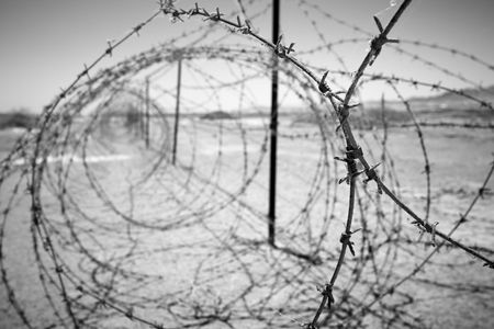 confined: barbed wire at the border of a mine field Stock Photo