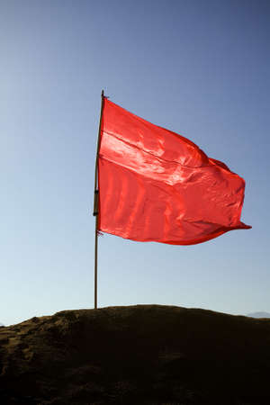 red flag on a hill against blue sky