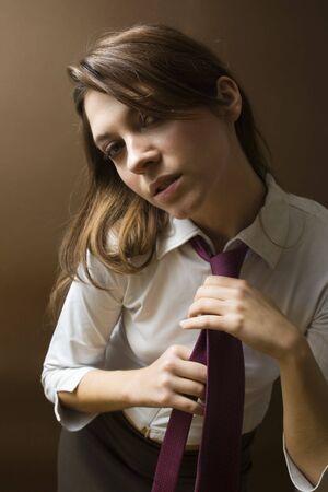 women at work: irritated businesswoman fixing her tie photo
