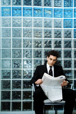 businesswear: hard worker: business man sitting in a waiting room and checking stocks