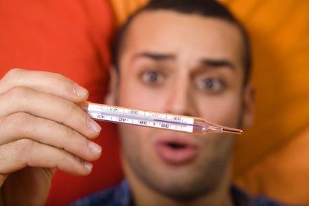 flu: healthcare and medicine: man taking his temperature