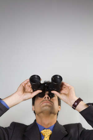 business vision: businessman looking up though binoculars Stock Photo
