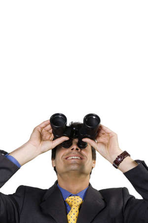successfulness: business vision: businessman looking up though binoculars, isolated on white