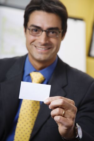 successfulness: work place: successful businessman smiling and holding a white card