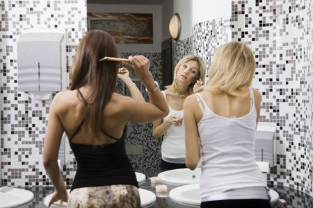 attractiveness: girls night out: girls applying makeup in the bathroom of a club