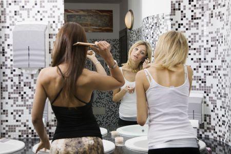 attractiveness: las ni�as la noche: la aplicaci�n de las ni�as de maquillaje en el ba�o de un club  Foto de archivo