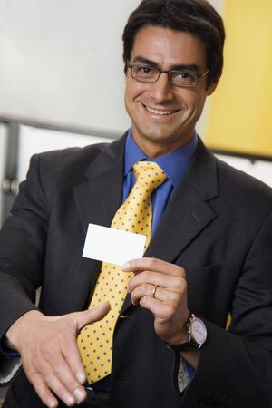 officeworker: work place: successful businessman smiling and holding a white card