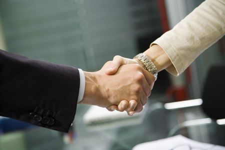 People at work: man and woman hand shaking at a meeting photo