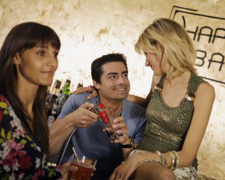 girls night out: girls night out: girls flirting with the barman Stock Photo