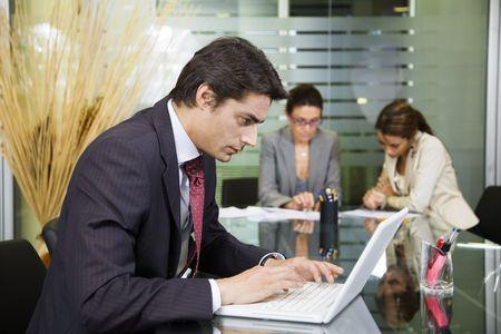 trabajando duro: La gente en el trabajo: hombre de negocios que trabajan con ordenador port�til durante una reuni�n
