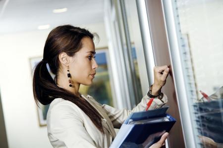 Office life: young secretary knocking on her bossÕ door  Stock Photo