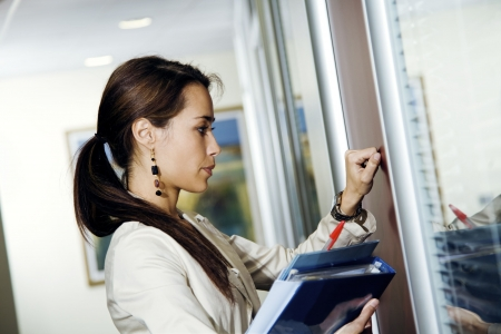 Office life: young secretary knocking on her boss� door
