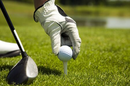 competitiveness: Golf club: golfer arranging the ball on the tee