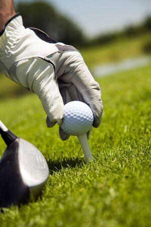 Golf club: golfer arranging the ball on the tee  photo