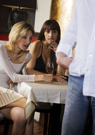 Girls night out: horny girls looking at a guy's backside  photo