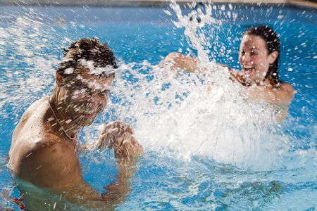 Healthy lifestyle: couple having fun at the swimming pool  Stock Photo