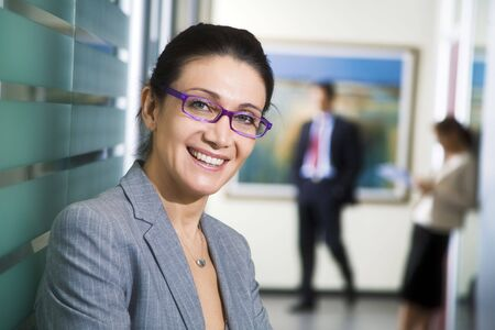 successfulness: Office life: young business woman looking at the camera smiling