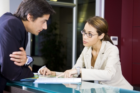 reception hotel: Office life: young salesclerk talking to a customer