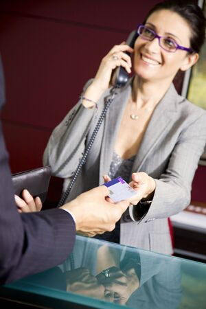 Paying by credit card: young salesclerk smiling at a customer Stock Photo - 1290439