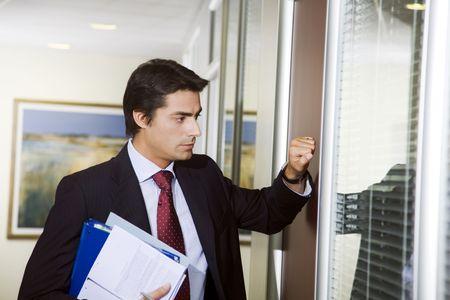 doorways: Office life: young employee knocking on his boss door