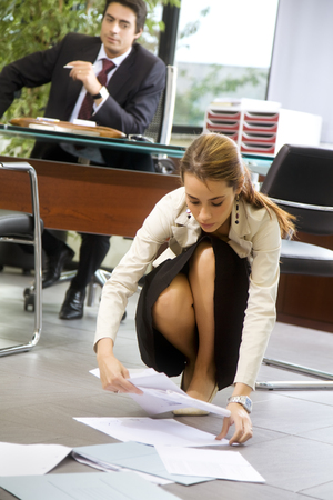 is embarrassed: Office life: exhausted secretary picking up some files   Stock Photo